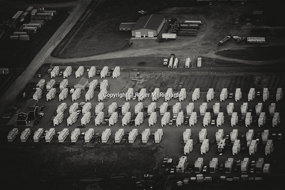A temporary housing area for oil workers, dubbed a 'man camp', viewed from the air. The Bakken Shale formation in North Dakota contains some of the richest deposits of oil and gas in the world. This has led to a boom in hydraulic fracturing (fracking) in the state and region, with considerable economic benefits but also negative consequences for residents way of life and environment of the area. Photo by Roger M. Richards