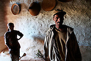 """A local man stands in his house with his daughter. Occupying a high plateau and bordering with Eritrea in the very north of Ethiopia lies the ancient Province of Tigray. It is an area widely considered to be the fulcrum of Ethiopian culture with towns dated to before the birth of Christ. Distinctively different from the rest of Ethiopia, strongly Orthodox Christian and culturally proud, Tigray is a mountainous and rocky region dotted with ancient churches carved in to sandstone cliffs. Filling these churches are old religious manuscripts and Bibles safe-guarded by protective Priests. Its remoteness has protected the culture as well as the religious sanctuaries that have been described as """"the greatest of the historical-cultural heritages of the Ethiopian people"""". But now Tigray is at a crossroads. Improved infrastructure has led to an opening up of even the remotest towns and villages. Signs of modernity such as internet cafes and cell phones are increasingly being used by younger Tigraians dressed in jeans and T-shirts. Yet the Church remains an ancient and powerful institution which protects its ancient customs creating scenes that haven't changed since Biblical times.."""