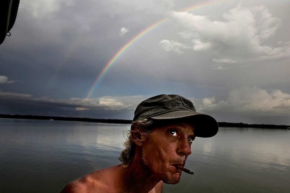 Scot Janikula looks West from the back of his houseboat to see if there will be a decent sunset as a rainbow appears behind him, the result of a summer storm in Estero Bay.