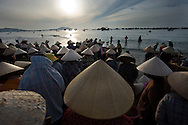 Vietnamese women wait for the small conical boats to arrive, so they can begin sorting and loading the fish to bring to market.