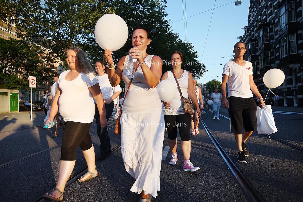 Nederland, Amsterdam , 23 juli 2014.<br /> Duizenden mensen lopen mee met een stille tocht door het centrum van Amsterdam. Volgens de organisatie zijn er zo'n vijfduizend deelnemers, meldt persbureau Novum. De wandeling begon om 20.00 uur op de Dam en eindigt daar ook weer. Deelnemers zullen daar witte ballonnen oplaten. Ook dragen zij witte kleding.<br /> Op de foto: De Stille tocht trekt over de Marnixstraat voorbij.<br /> Thousands of people in white clothes walk along with a silent march through the center of Amsterdam. The victims of flight MH17 are thus commemorated. National day of Mourning .