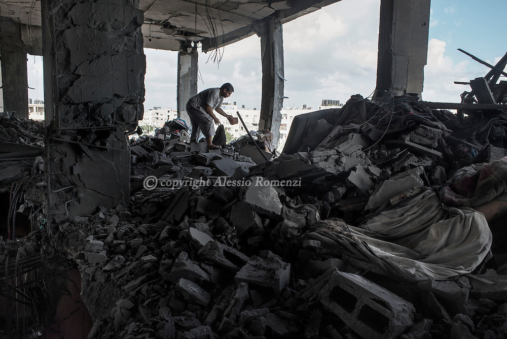 Gaza Strip, Gaza City: A Palestinian man searches amidst rubbles of his house destroyed by an overnight Israeli airstrike in Sheik Said neighborhoud. ALESSIO ROMENZI