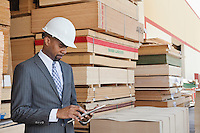 African American male contractor using tablet PC with stacked wooden planks in background