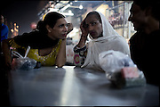 "Chabbo, age 32, F., 28, and K. (left to right), 28 years old, both transvestites, wait for their mixed chai in the street food market. Most of the transvestites people live an extremely marginalized life, for many reasons they create a kind of community in alternative to the pakistani society Evening in Lahore, Pakistan on Wednesday, December 03 2008.....""Not men nor women"". Just Hijira, Kusra. Painted lips, Kajal surrounding their eyes and colourful veils..Pakistan is today considered a strongly, foundamentalist as well, islamic country. But under its reputation, above all over the talebans' continuos advancing, stirs a completely extraneous world, a multiethnic mixed society. Transvestites make part of it, despite this would not be admitted by a strict law. Third gender, the Hijira are born as men (often ermaphrodites) or with an ambiguous genital situation, and they have their testicles and penis removed through a - often brutal - surgical operation. The peculiarity is that this operation does not contemplate the reconstruction of a female organ. This is the reason why they are not considered as men nor women, just Hijira. They are often discriminated, persecuted  and taxed with being men prostitutes in the muslim areas. The members of this chast perform dances during celebrations, especially during weddings, since it is anciently believed that an EUNUCO's dance and kiss in the wedding day brings good luck to the couple's fertility...To protect the identities of the recorded subjects names and specific .places are fictionals."