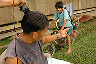 A man looks at his reflection in a broken mirror while receiving a  hair cut in the yard outside his thatched hut in the Mayan village of Midway, Belize.  A boy on a bike looks on. The razor is electric, a new feature with the recent introduction of electricity in the village.