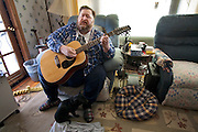 Rick Bumgardener, a self-taught gospel singer, guitar player, and lay preacher, sings an original song, ?Give Us Barabbas,? at his home in Halls, Tennessee while his dog, Bear lies at his feet. (From the book What I Eat: Around the World in 80 Diets.) The caloric value of his day's worth of food in the month of February was 1,600 kcals. He is 54; 5 feet nine inches tall,  and 468 pounds. Rick used to enjoy preaching and playing on Wednesday evenings at Copper Ridge Independent Missionary Baptist Church before he became too heavy to stand for long periods. Rick's new lifestyle rules out one of his favorite restaurant dinners with his wife, Connie, and son, Greg: three extra-large pizzas, crazy bread, and no vegetables. There would be leftovers, but not for long, Rick says, as he would eat all of them. To relieve boredom, he wakes up late, plays video games, plays his guitar, and watches TV until the early hours of the morning. MODEL RELEASED.