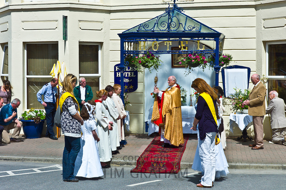 Priest carries Blessed Sacrament in Corpus Christi catholic traditional Benediction ceremony in Clifden, County Galway, Ireland