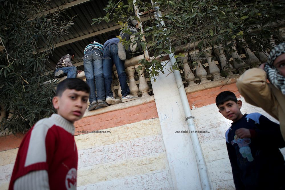 Chlidren try to get on the top of the mosques wall to get a glimpse of the seven bodies lying inside the mosque in Idlib, Province of Idlib, Syria.