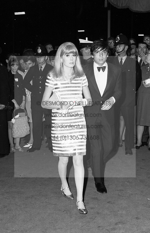DAVID BAILEY and CATHERINE DENEUVE at the gala premier of Kaleidoscope at the Warner Theatre, Leicester Square, London on 9th September 1966.