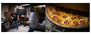 Left: Andy Bollin(right), of Hanover, chats with his delivery driver, Chris Cramer, of Littlestown, during downtime at his store, Pizza 2 U, Saturday, Jan. 20, 2018 in Littlestown, PA. Bollin has owned the small-town pizza store for five years, buying it after quitting his job working in a pizza shop to be his own boss. Right: Pizza exits the oven, Saturday, Jan. 20, 2018.