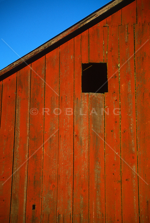 Red barn with one window against a blue sky