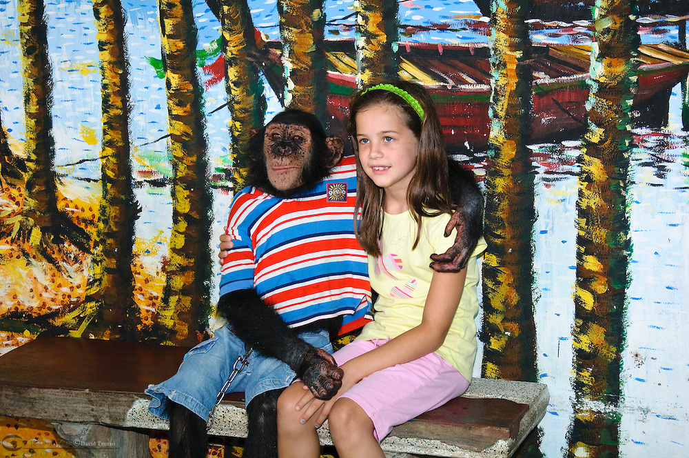 Girl age 7-8-9, poses with a monkey at Samphran Elephant Ground & Zoo Nakhon Pathom province Thailand