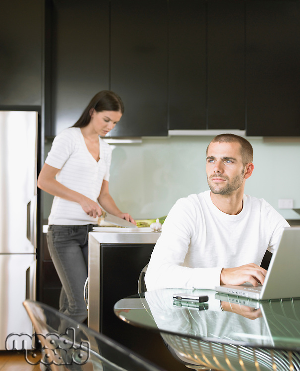 Man on computer woman chopping food in modern kitchen