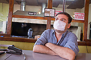 Apr. 27, 2009 -- NOGALES, SONORA, MEXICO: A bar tender, wearing a mask to protect him from the swine flu,  in Nogales, Sonora, Mexico, waits for customers in his empty bar. The Mexican government broadened its efforts to control the outbreak of swine flu Monday closing schools throughout the country. In Nogales, on Mexico's northern border with the US, people started wearing masks as news of the outbreak spread.  Photo by Jack Kurtz