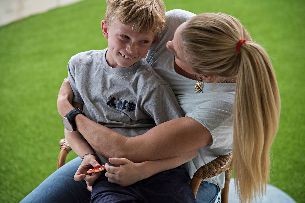 Kerri Walsh Jennings takes a break from her on-camera interview ESPN's Sportscenter, to hug her oldest son Joey, 8, after he arrived home from school
