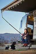 A woman and her dog sit near the doorstep of thier RV trailer while camping in the desert of California.