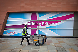 """© Licensed to London News Pictures. 30/09/2012. Manchester, UK . A man with a rubbish cart walks by a the Labour Party's slogan for the event , """" Rebuilding Britain """" . Labour Party Conference Day 1 at Manchester Central . Photo credit : Joel Goodman/LNP"""