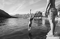 A young man dives into Kotor Bay in Montenegro, soon to be followed by his friend.