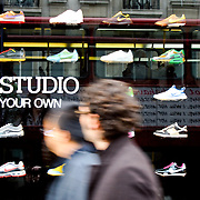 Window display in a shoe shop in London's Oxford Street with a red London bus reflected. Oxford Street is the heart of London high street shopping.