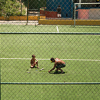 An adult helps patch up Santa Marta's football pitch.