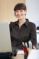 Woman wearing headset at desk in office portrait