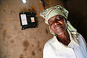 Elizabeth Mukwimba is a 62-year-old Tanzanian woman who now has solar lighting and electricity in her home at the flick of a switch, thanks to a scheme backed by UK aid.<br /> <br /> Elizabeth has had an M-Power solar panel and lights fitted in her home by Off Grid Electric, a private sector company dedicated to providing sustainable, affordable energy to people in developing countries who aren't connected to the electricity grid. <br /> <br /> It means that Elizabeth now has lighting at home at night, which means she doesn't have to buy expensive kerosene. The money she's saved already has helped her put a new tin roof on her house. It also means her grandchildren can read and do their homework in the evening.<br /> <br /> UK aid is providing support to help Off Grid Electric expand its business to reach more and more people who live in remote, rural areas, through two international partnership programmes - Energising Development (EnDev), and the Africa Enterprise Challenge Fund Renewable Energy and Adaptation to Climate Technologies (AECF REACT).<br /> <br /> The UK's support to EnDev is a 'results based financing' facility - this provides a financial incentive for companies like Off Grid - meaning they only get access to finance if they meet a given target (increasing the number of people who have access to clean energy) over a fixed period of time. This acts to boost the market returns for private sector companies providing services to poorer consumers, thereby attracting investment and enabling continued market expansion after the project (and financial incentive) ends.<br /> <br /> In less than 2 years, Off Grid Electric has installed solar power systems in over 22,000 homes across Tanzania, meaning many more people now have access to cheap, renewable electricity - a vital step forward in a country where less than 14% of the population are connected to the electricity grid.<br /> <br /> Picture: Russell Watkins/Department for International Development.