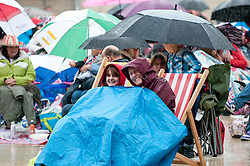 © Licensed to London News Pictures. 03/06/2012}. Bristol, Uk. Bristol residents brave the rain in Millennium Square for a screening of the pageant during the Royal Jubilee celebrations. Great Britain is celebrating the 60th  anniversary of the countries Monarch HRH Queen Elizabeth II accession to the throne this weekend Photo credit :David mirzoeff/ LNP