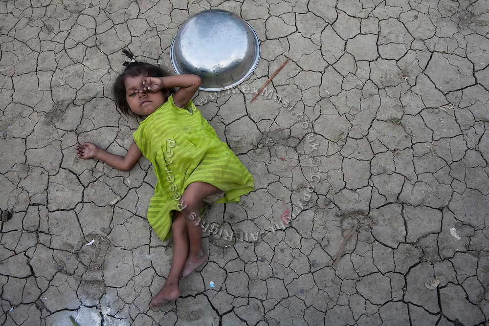 Meenakshi, 6, a child born with mental and physical disabilities from a gas-affected mother, is lying on the dry ground in front of her home in the impoverished Oriya Basti Colony, Bhopal, Madhya Pradesh, near the abandoned Union Carbide (now DOW Chemical) industrial complex.
