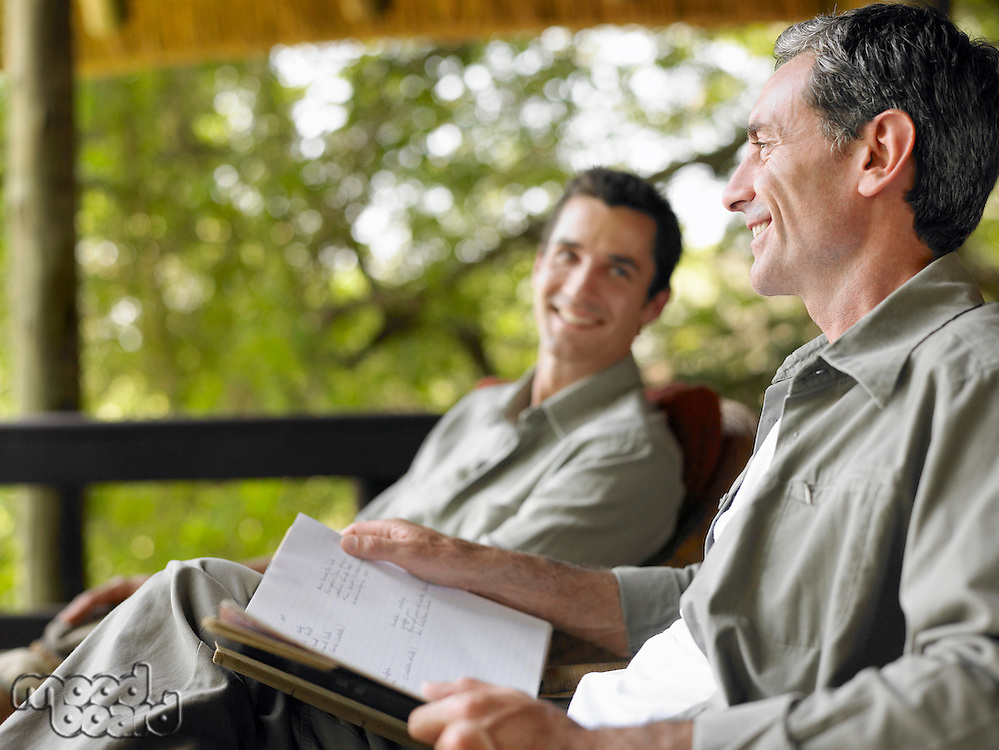 Two men sitting on terrace smiling one holding book
