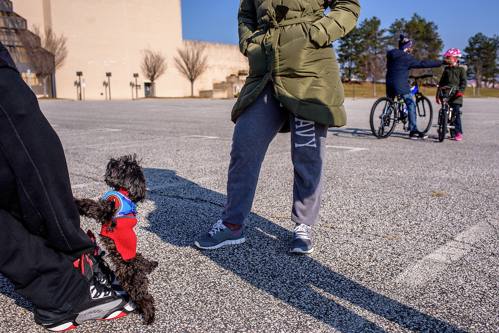 Owings Mills, Maryland - December 21, 2014: Marcus Ragsdale, 34, and Katrina Ragsdale, 28, take their children, Marcus, 12, Chance, 7, and Diggy, their two-year-old yorkie-poodle to the vacant parking lot at the Owings Mills Mall where the Boscov's department store formerly occupied.<br /> Owings Mills Mall, located in Owings Mills, Maryland, is a dying mall. The expansive parking lots are sparse, considering it's the Sunday before Christmas. The majority of stores in the mall are vacant. JCPenney and Macy's are the mall's remaining anchors. <br /> CREDIT: Matt Roth for The New York Times<br /> Assignment ID: 30168685A