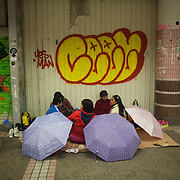 A group of Filipino women sit and chat and eat oin the street in Hong Kong Central on a Sunday evening. Hong Kong has a huge Filipino population, most of them women working as domestic servants. They meet in public on their days off since none of them have their own private accomodation. 7 million people live on 1,104km square, making it Hong Kong the most vertical city in the world.
