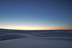 The calm white dunes of White Sands National Monument in New Mexico appear to glow blue beneath the sunrise.