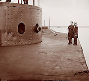 "Civil War: James River, Va. Deck and turret of the battle damaged U.S.S. Monitor. It shows marks of enemy fire from the Merrimack (CSS Virginia, dents on turret) James Gibson photographer. She was made famous in the historic Hampton Roads ""Battle of the Ironclads Monitor vs Merrimack"". 1862 July"