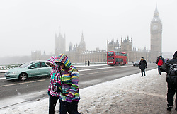 © Licensed to London News Pictures. 20/01/2013. London, UK.  People cross Westminster Bridge,central London, amidst snowy conditions with Big Ben & the Houses of Parliament as a backdrop. Photo credit : Richard Isaac/LNP