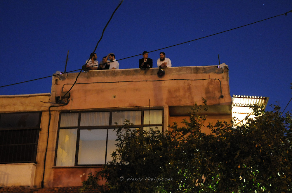 Israeli settlers and ultra-orthodox jewish stand on the roof of the Ghawil family house that the settlers are occupying ever since the forceful eviction of the Palestinian families on the 2nd of August of 2009