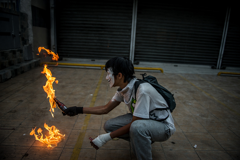 CARACAS, VENEZUELA - MAY 22, 2017:  Anti-government protesters use homemade shields and throw rocks and molotov cocktails at security forces, who responded by heavily tear gassing and firing rubber bullets and buckshot at them.  The streets of Caracas and other cities across Venezuela have been filled with tens of thousands of demonstrators for nearly 100 days of massive protests, held since April 1st. Protesters are enraged at the government for becoming an increasingly repressive, authoritarian regime that has delayed elections, used armed government loyalist to threaten dissidents, called for the Constitution to be re-written to favor them, jailed and tortured protesters and members of the political opposition, and whose corruption and failed economic policy has caused the current economic crisis that has led to widespread food and medicine shortages across the country.  Independent local media report nearly 100 people have been killed during protests and protest-related riots and looting.  The government currently only officially reports 75 deaths.  Over 2,000 people have been injured, and over 3,000 protesters have been detained by authorities.  PHOTO: Meridith Kohut