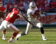 Oakland Raiders running back Justin Fargas (25) rushes up field against pressure from Kansas City Chiefs defensive back Ty Law (24) in the fourth quarter at Arrowhead Stadium in Kansas City, Missouri, November 19, 2006.  The Chiefs beat the Raiders 17-13.<br />