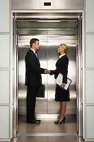 Businesspeople shaking hands in Elevator side view