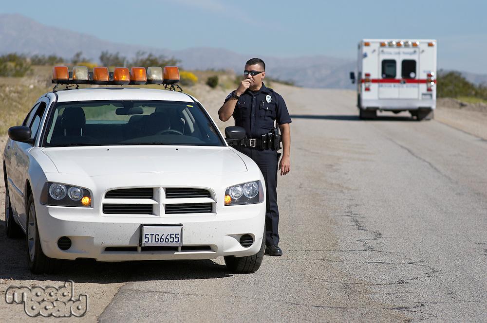 Police officer using CB radio on desert road