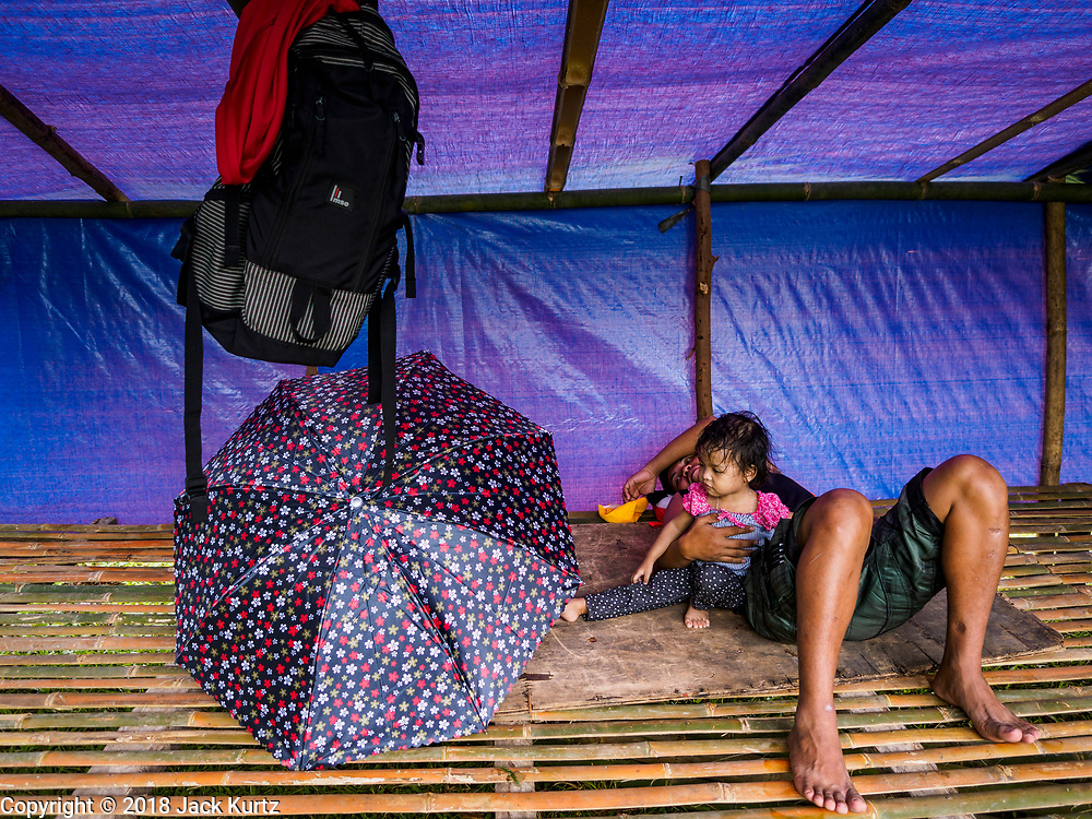 26 JANUARY 2018 - SANTO DOMINGO, ALBAY, PHILIPPINES: A family in their temporary shelter in a field in Santo Domingo. The family lives on the slopes of the Mayon volcano and was evacuated because of the volcano's recent eruptions. The volcano was relatively quiet Friday, but the number of evacuees swelled to nearly 80,000 as people left the side of  the volcano in search of safety. There are nearly 12,000 evacuees in Santo Domingo, one of the communities most impacted by the volcano. The number of evacuees is impacting the availability of shelter space. Many people in Santo Domingo, on the north side of the volcano, are sleeping in huts made from bamboo and plastic sheeting. The Philippines is now preparing to house the volcano evacuees for up to three months.        PHOTO BY JACK KURTZ