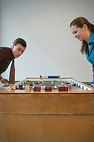 Young man and woman playing table football in games room