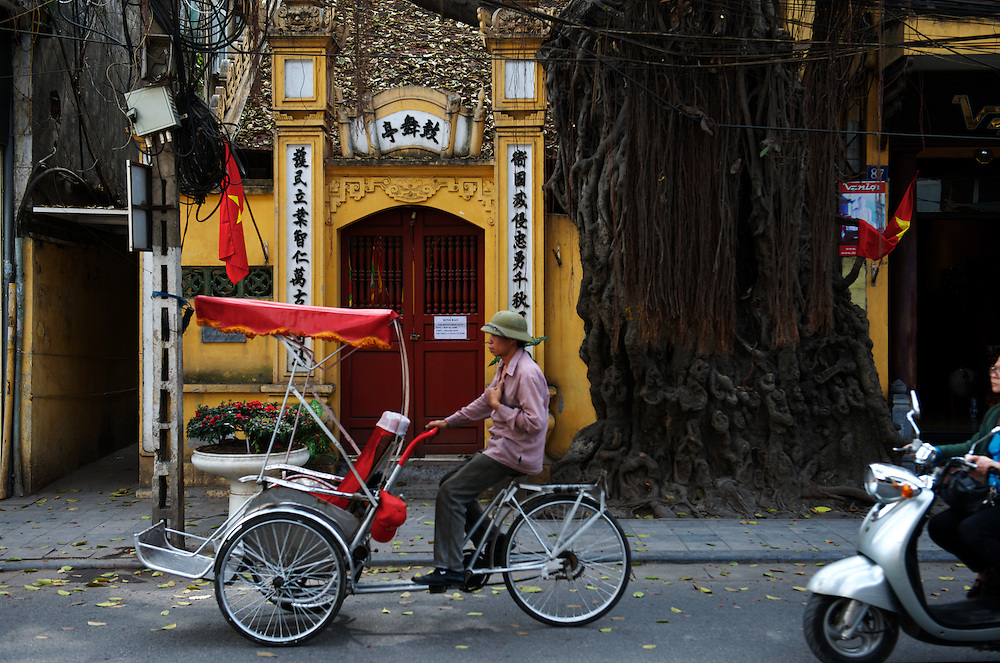 """A """"cyclo"""" driver passes one of Hanoi's many family shrines, wearing the traditional hat, Old Quarter."""