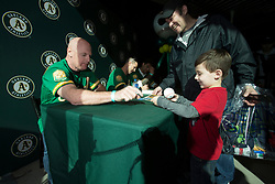 New Oakland Athletics third base coach Matt Williams, left, signs a ball for five-year-old Kyle Sanchez of Martinez, Calif. while dad Daniel watches, during Oakland Athletics FanFest at Jack London Square on Saturday, Jan. 27, 2018 in Oakland, Calif. (D. Ross Cameron/SF Chronicle)