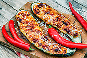 Wooden board with fresh baked filled zucchini decorated with parmesan cheese and chili peppers.