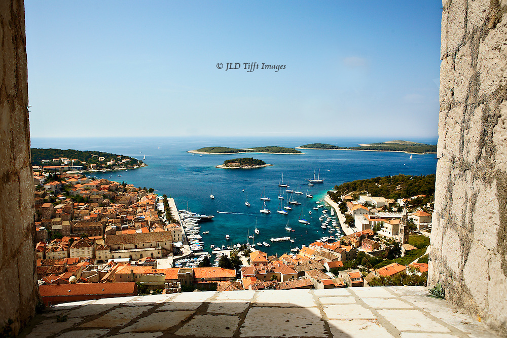 View from Hvar hilltop castle embrasure over the town and harbor below, at noon on a sunny day.