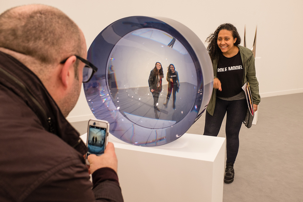New York, NY - May 3, 2019. Spectators have fun with Fred Eversley's untitled cast polyester pieces at the David Kordonskky Gallery at the Frieze Art Fair on New York City's Randalls Island.