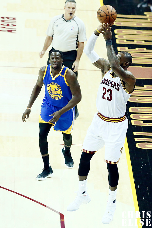 07 June 2017: Cleveland Cavaliers forward LeBron James (23) takes a jump shot over Golden State Warriors forward Draymond Green (23) during the Golden State Warriors 118-113 victory over the Cleveland Cavaliers, in game 3 of the 2017 NBA Finals, at  the Quicken Loans Arena, Cleveland, Ohio, USA.