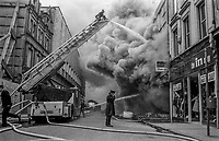 Fire appliance with turntable ladder is used to combat a fire in Arthur Square, Belfast, N Ireland, following explosion of a Provisional IRA bomb. March 1974. 19740300090a<br />