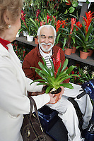 Senior woman showing potted flower to elderly man in garden center