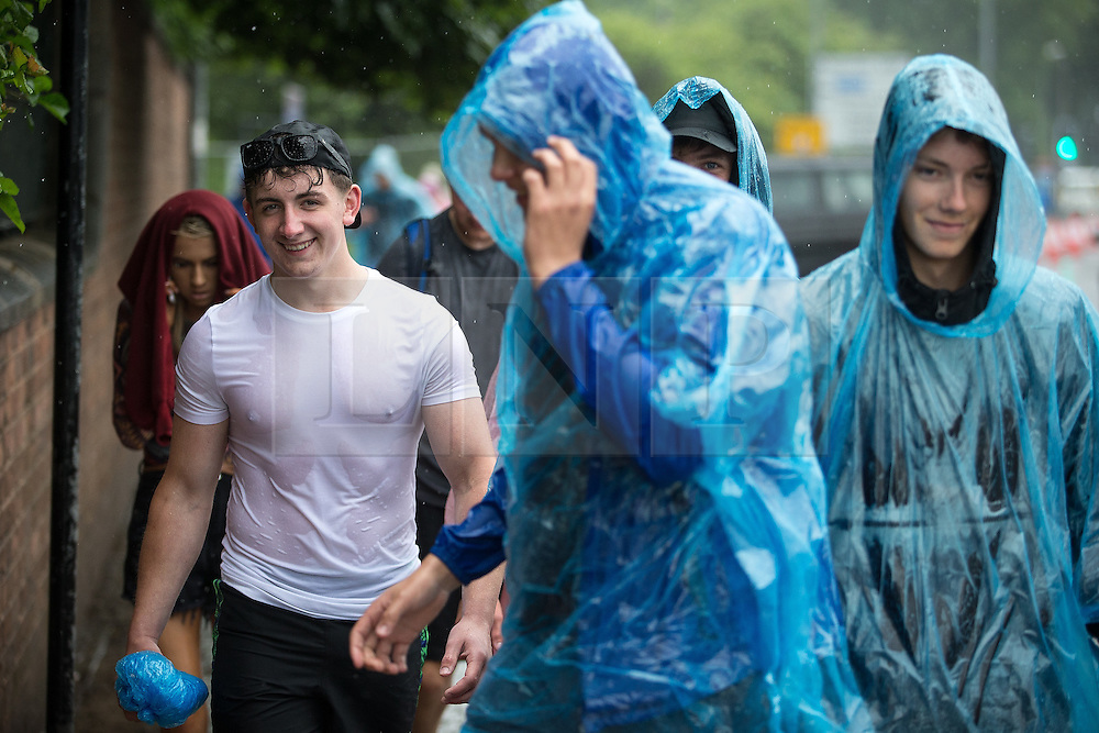 © Licensed to London News Pictures . 11/06/2016 . Manchester , UK . Revellers arrive at the festival in a heavy downpour . Parklife music festival at Heaton Park in Manchester . Photo credit : Joel Goodman/LNP